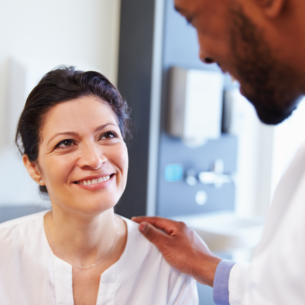 Woman in healthcare setting talking to her doctor